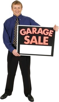 man holding garage sale sign