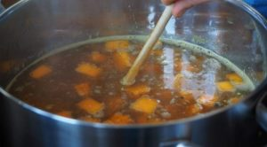 carrots onions and parsley simmering in a pot