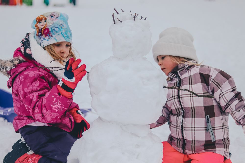 two girls building a snowman